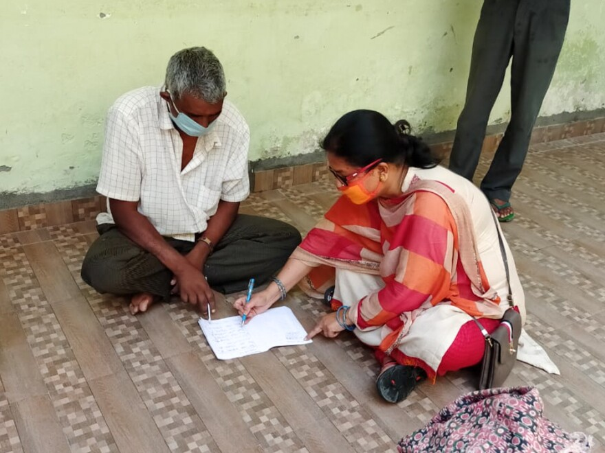 Prema Thakur, an official for the Champawat district in India, teaches Pratap Singh Bora, a 56-year-old migrant laborer from Nepal, how to write his name in Hindi.