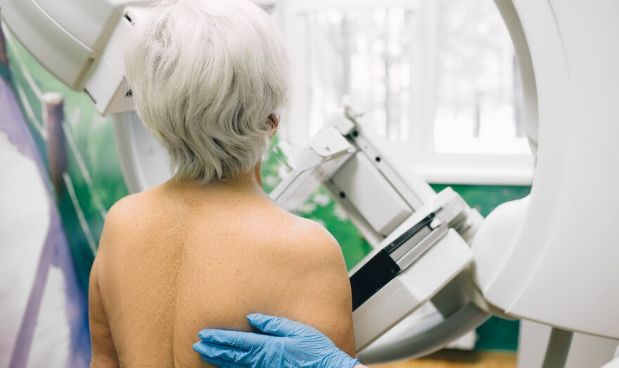 a short haired person with their back turned to the viewer gets their breast imaged on a mammogram machine