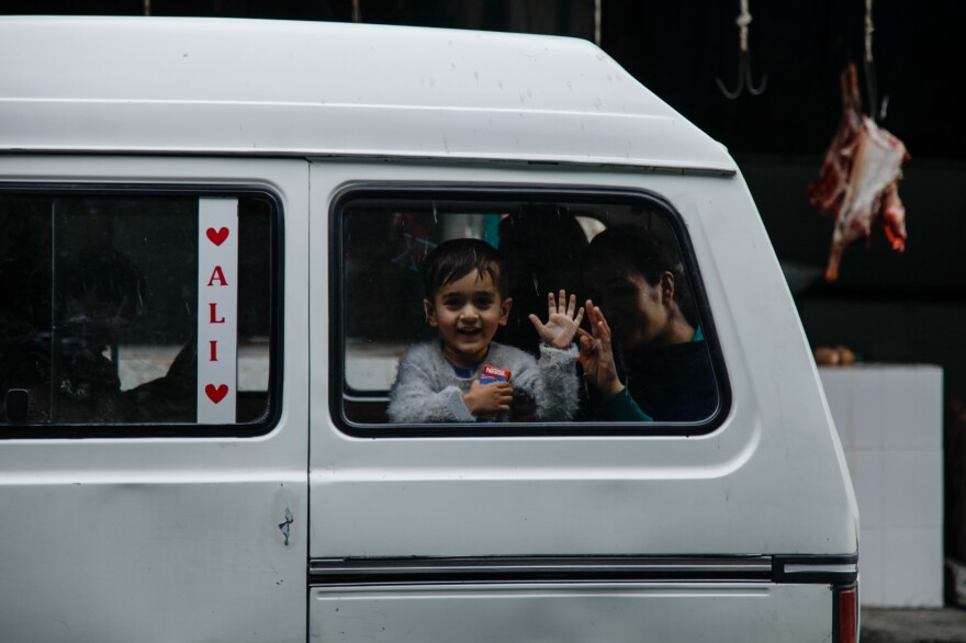 A child waves to tourists from a minivan in a small town in far northern Pakistan. Some tourists' behavior is unwelcome in the area.