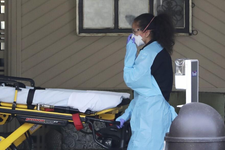 An ambulance worker adjusts her protective mask