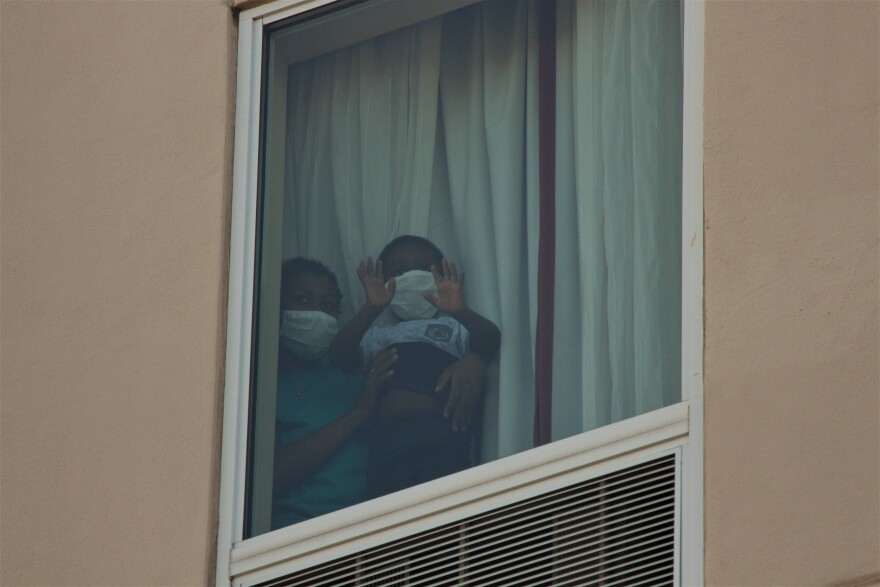Migrants peek out of the window of the fourth floor of a Hampton Inn in McAllen on July 23.