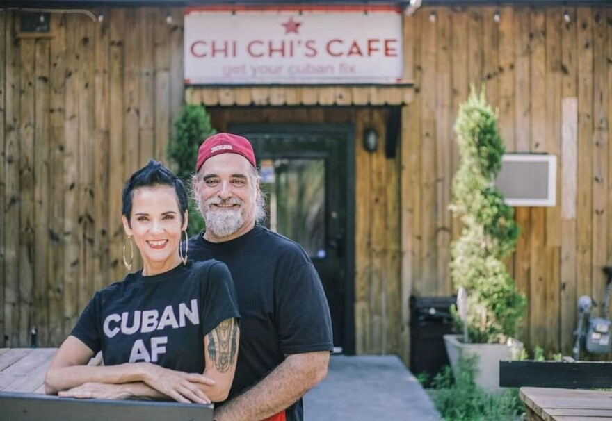 "Chi Chi stands next to her husband. She's wearing a T-shirt with letters that read, ""Cuban AF."" Her husband stands next to her. He's wearing a backwards baseball cap and a T-shirt. Behind them is a sign that read's Chi Chi's Cafe."
