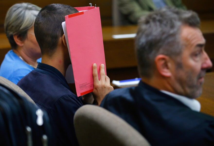 A man identified only as Daniel K. covers his face with a folder as he sits in a courtroom in Cologne, Germany, on Friday.