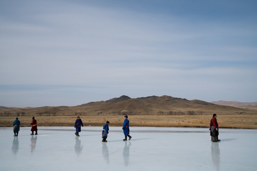 People tread carefully on the smooth ice. The competition, originally scheduled for mid-March, was bumped up by two weeks because the river had begun to show early signs of melting.