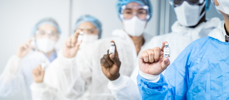 A group of doctors in protective gear holding bottles of a vaccine.