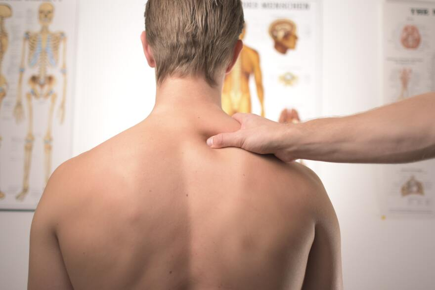 doctor checking patient's spine