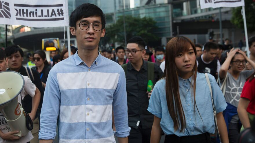 "Sixtus ""Baggio"" Leung (left) and Yau Wai-ching (right) of the Youngspirations party march during a protest in Hong Kong on Sunday. Hong Kong police used pepper spray to drive back hundreds of protesters angry at China's decision to intervene in a row over whether the two pro-independence lawmakers should be barred from the city's legislature."