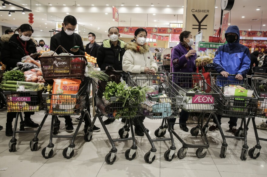 Residents of Wuhan China wear masks to buy vegetables in the market on January 23th, 2020.