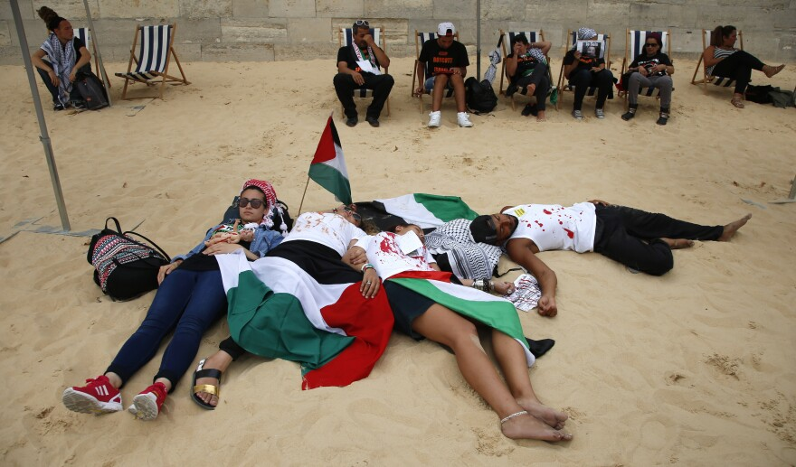 """Pro-Palestinian activists stage a die-in protest at their """"Gaza beach event,"""" held near the official Tel Aviv beach event on the banks of the Seine in Paris."""