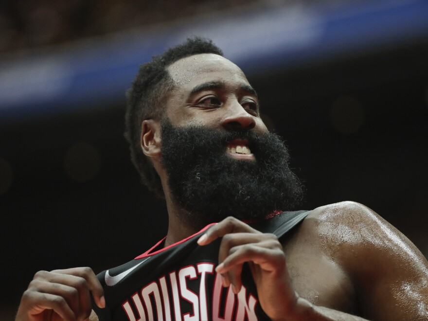 Houston Rockets' James Harden smiles during the first half of an NBA preseason basketball game against the Toronto Raptors.