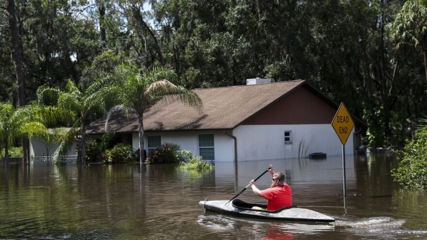 Man kayaks back to his Valrico home for more belongings, in flood waters from the Alafia River, after Hurricane Irma in September 2017.