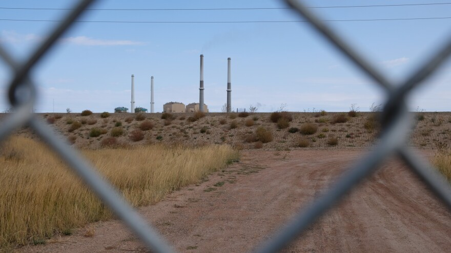 The four stacks of the Colstrip coal fired power plant seen from a distance through a chain link fence.
