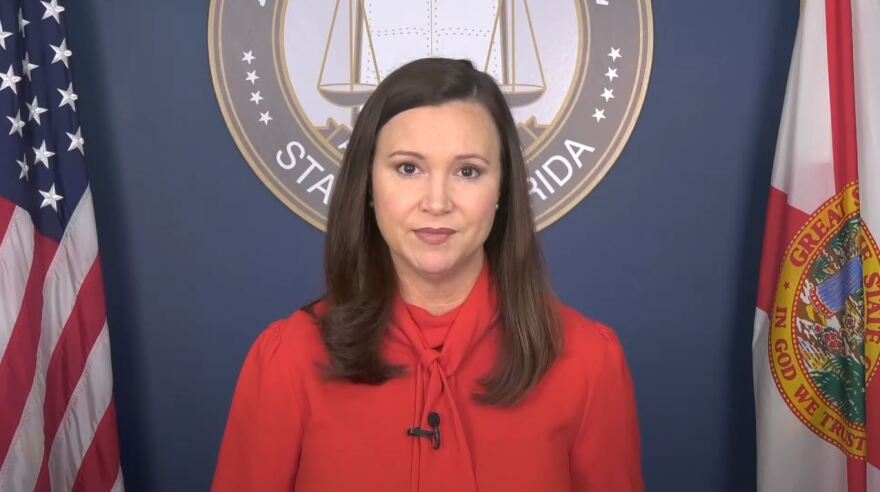 """Florida Attorney General Ashley Moody stands to look at the viewer. Behind her to the left is the American flag and to the right, is the Florida flag. Directly behind her is a seal that reads """"State Of Florida."""" Moody wears a jacket."""