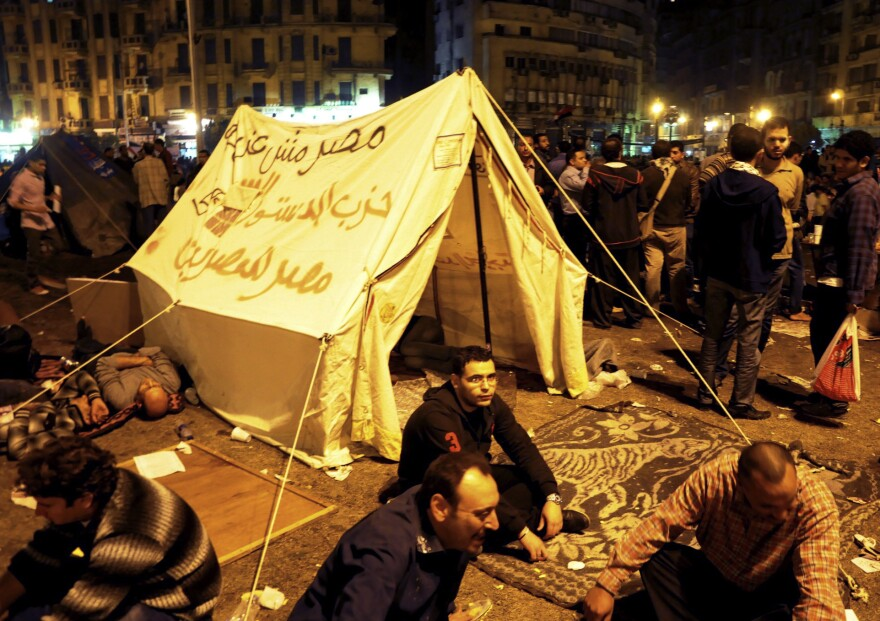"""Pro-democracy demonstrators occupy Cairo's Tahrir Square on Friday night. The writing on the tent reads, """"Egypt is not a farm, Constitution party, Egypt for Egyptians."""""""