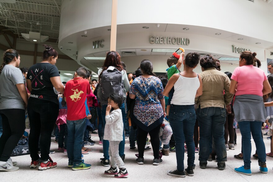 Migrants wait to receive bus tickets to destinations across the country. Adults wear ankle monitors so the government can ensure they check in with immigration officials once they reach their sponsors.
