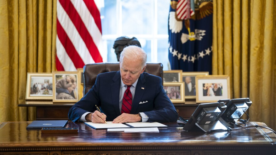 Biden signs executive actions in the Oval Office of the White House on January 28.