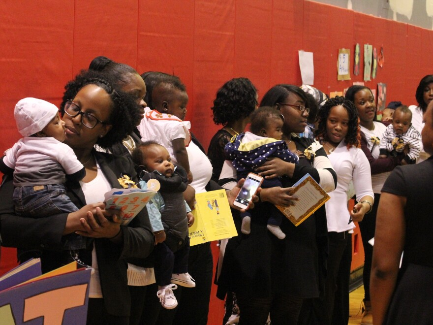 A group of mothers and infants celebrate a recent graduation from the Harlem Children's Zone Baby College program.