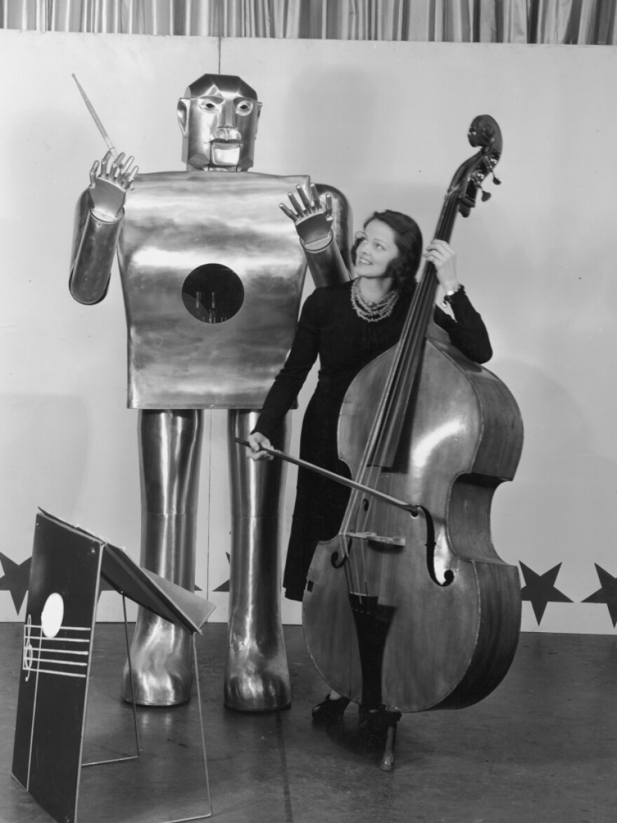 """Musician Lois Kendall plays the bass while the robot Elektro """"conducts"""" on stage as part of a Westinghouse Electric and Manufacturing demonstration at the 1939 World's Fair in New York."""