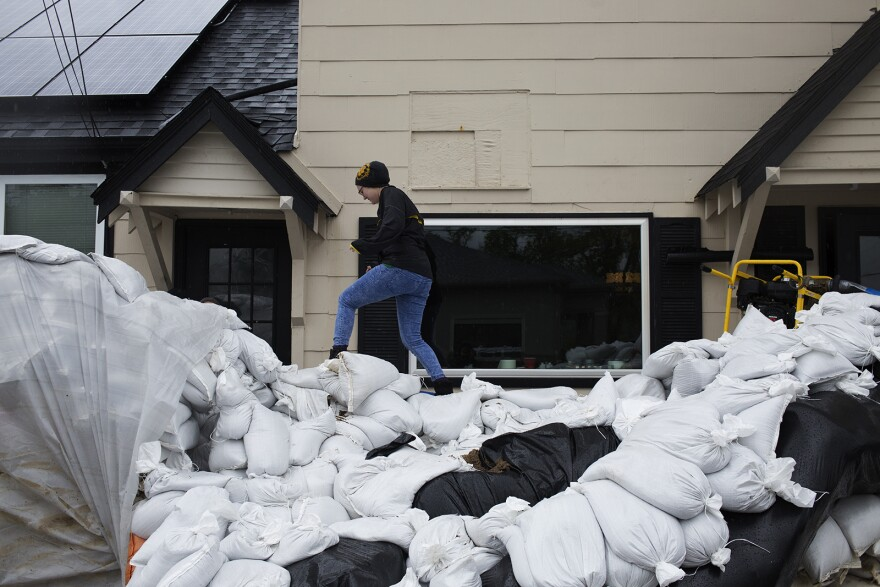 Employees of O'Dell's Irish Pub & Ale House in Eureka climb over a wall of sandbags to get into the bar Thursday afternoon.