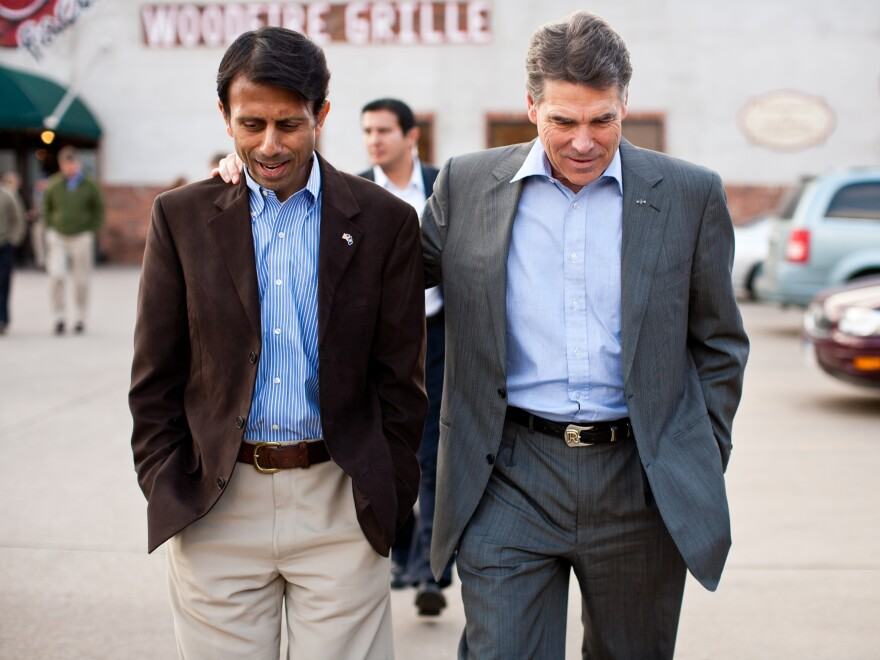 Louisiana Governor Bobby Jindal and Texas Governor Rick Perry walk together after a campaign meet and greet at The Button Factory restaurant on December 21, 2011 in Muscatine, Iowa.