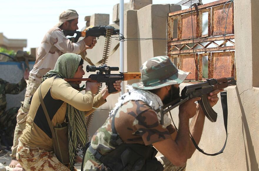 Iraqi pro-government fighters hold position in al-Shahabi village, east of Fallujah, on Wednesday, as part of a major assault to retake the city from Islamic State.