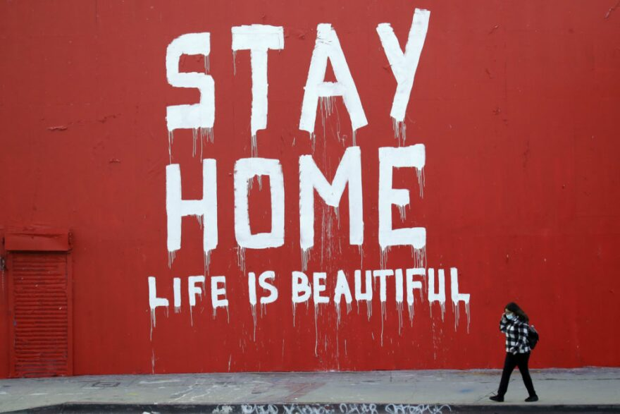 """A pedestrian walks past a mural which reads """"Stay at Home, Life is Beautiful"""" Thursday, April 2, 2020, in Los Angeles. (Marcio Jose Sanchez/AP Photo)"""