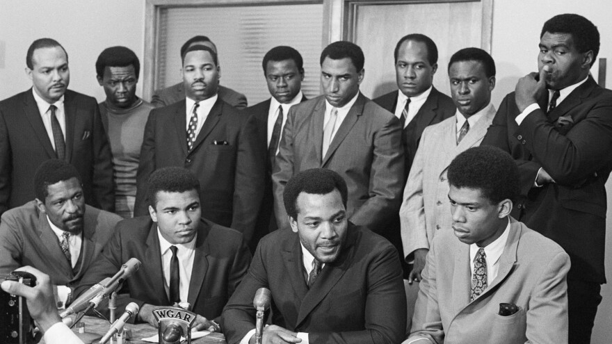 In this 1967 photo, black athletes gather for a meeting to hear Ali's view on rejecting Army induction. The photo shows: (front row) Bill Russell; Ali; Jim Brown and Lew Alcindor. Back row (left to right): Carl Stokes (Democratic state representative), Walter Beach, Bobby Mitchell, Sid Williams, Curtis McClinton, Willie Davis, Jim Shorter and John Wooten.
