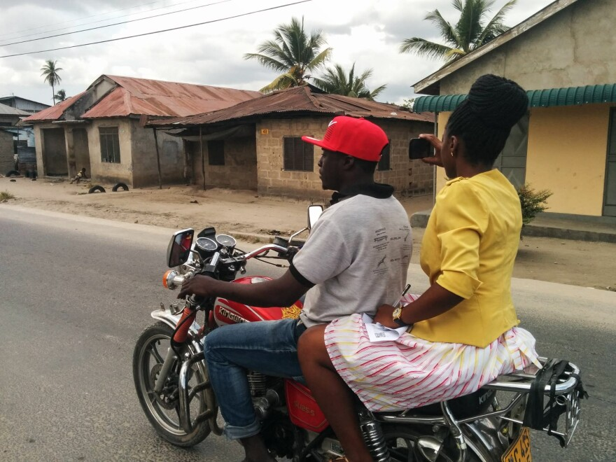 Beata Felix Rutabingwa, a World Bank consultant, captures street photos on a motorcycle in Dar es Salaam, Tanzania.