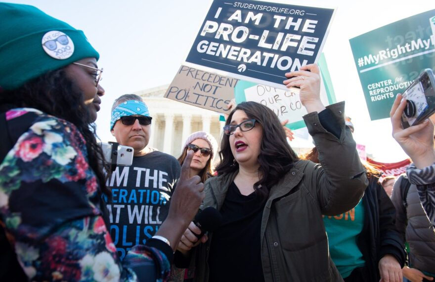Anti-abortion protesters and pro-choice activists supporting legal access to abortion protest speak to each other during a demonstration outside the Supreme Court