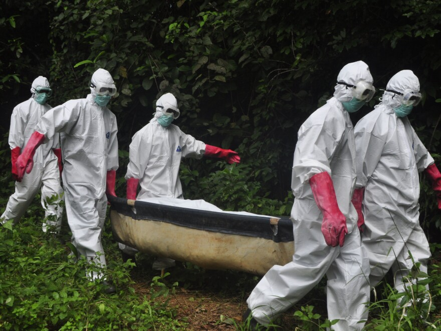A burial team carries the body of woman suspected to have died from the Ebola virus in Monrovia, Liberia. Most of the organized burial teams in the country are assisted by the aid group Global Communities, which, among other things, trains workers to properly wear personal protective equipment, like the gear this team is wearing.