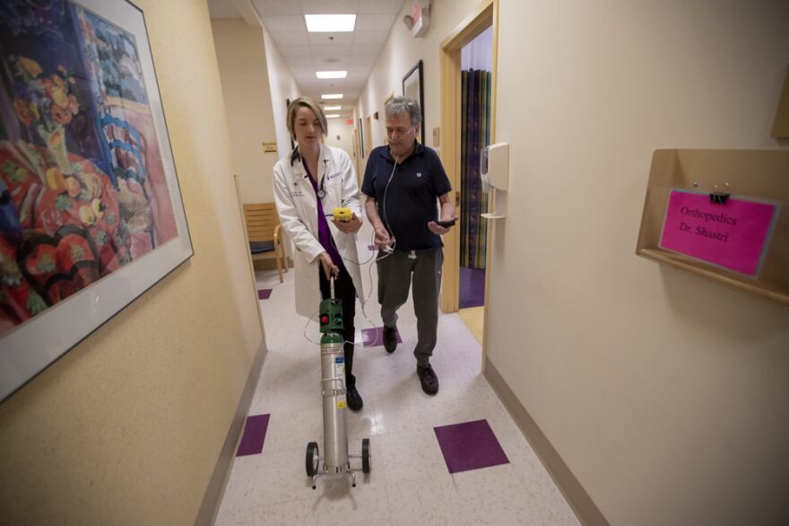 Dr. Mary Rice walks with Michael Howard at a Beth Israel Deaconess HealthCare clinic in Chealsea, Mass, as they test his oxygen levels with the addition of oxygen from a portable tank. He has COPD, a progressive lung disease that can be exacerbated by heat and humidity.