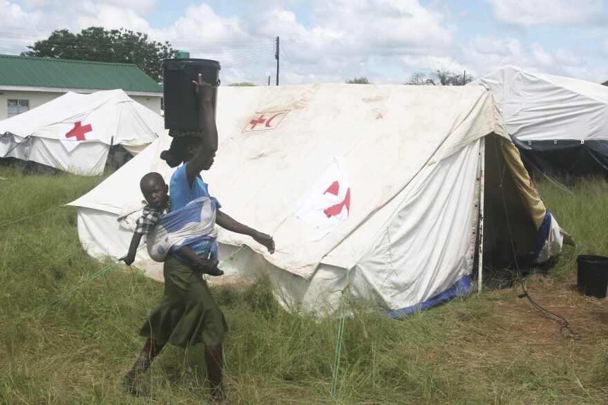 A woman carrying her baby walks past a tent in Zimbabwe after being rescued from floodwaters last month. The African country has been hit by heavy rains and a tropical cyclone, and about 250 people have been killed since October, according to the government.