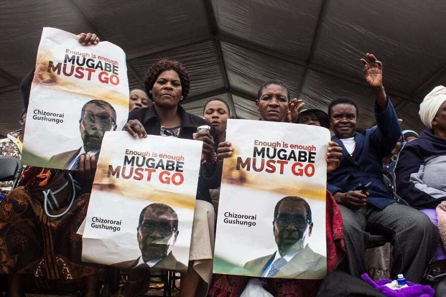 Female war veterans from the liberation struggle hold up placards urging Mugabe to step down during a mass march that saw tens of thousands protest in November 2017.