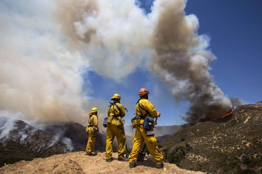 Firefighters keep watch at Green Valley as the fire has burned more than 1,400 acres since Thursday in the Angeles National Forest just north of Castaic, in California.