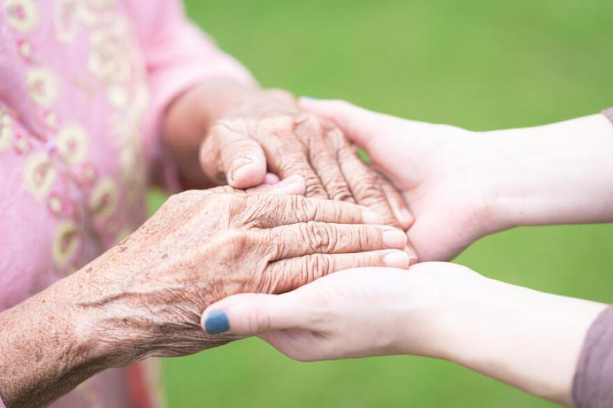 Close up image of young woman holding wrinkled hands of senior elderly woman with care