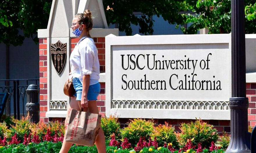 A woman walks past a sign at the University of Southern California (USC) in Los Angeles, California where coronavirus cases have seen an alarming increase with more than 100 students in quarantine from cases originating in off-campus housing.
