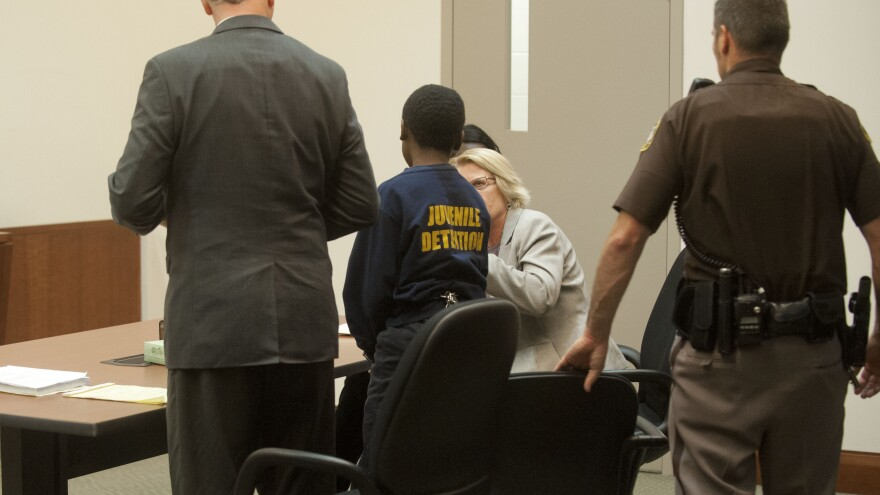 A 12-year-old on trial in the stabbing death of a 9-year-old talks to his lawyer in 2014 in a Michigan circuit court. The Justice Department is targeting a Georgia case in the hopes of making legal representation for juveniles there more effective, but they say the problems occur nationwide.