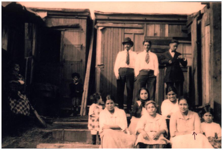 Gonzales and Zuniga spoke for hours piecing together some of the history of St. Louis' early Mexican residents. They found places where the county's archives overlapped into Zuniga's family life — like this picture. Multiple families gather in front of a