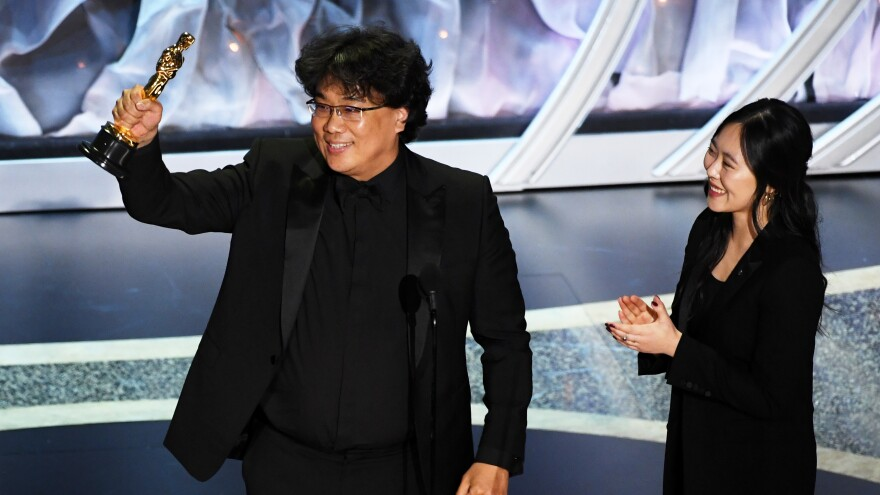 Bong Joon-ho, here with interpreter Sharon Choi, won big at Sunday's Oscars. His film <em>Parasite</em> took best international feature and best picture, and he was recognized for his direction and writing.