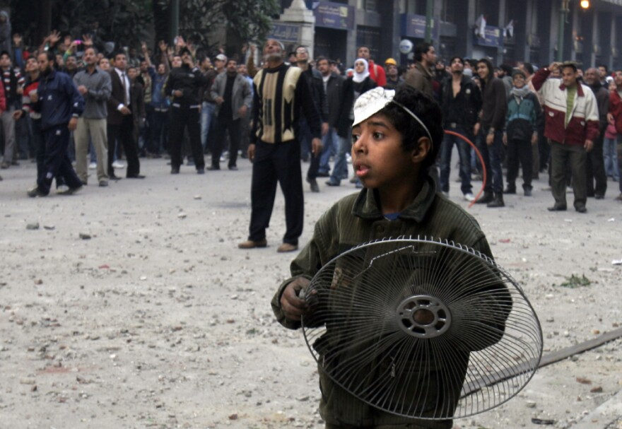 A youthful protester holds a fan cover to protect himself from rocks during clashes with military police near Tahrir Square in Cairo on Friday.
