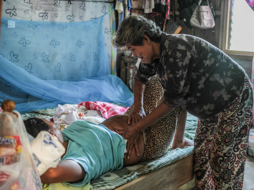 Florida Domingo massages Calibuso's belly. The early morning massage is part of a traditional healing process after delivery.
