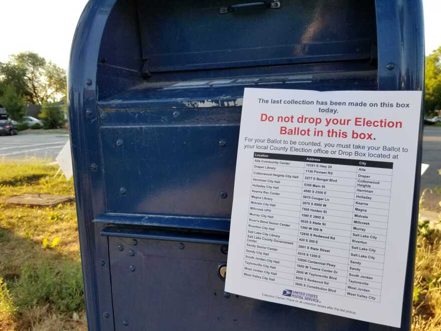 Photo of USPS mail box with an election sign telling voters not to drop ballots here.