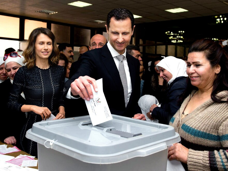 Syrian President Bashar Assad, flanked by his wife, Asma (left), casts his ballot in the parliamentary elections Wednesday in Damascus, Syria, in a photo released on the official Facebook page of Syrian presidency.
