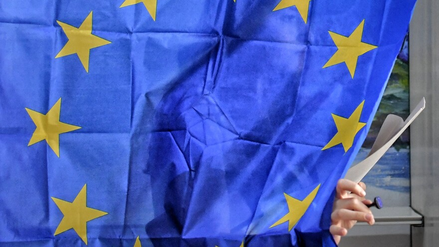A woman exits a voting booth with curtains depicting the European Union flag in Baleni, Romania, on Sunday.