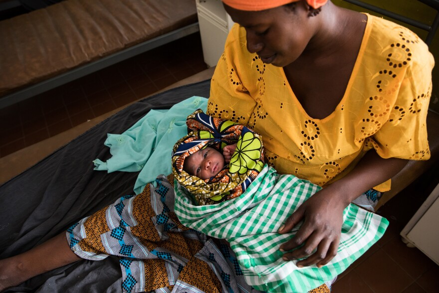"Naba Dabo, 25, holds her day-old baby at the maternity ward of the Brufut Minor Health Center outside of Banjul in the Gambia. The midwives at the clinic say that they don't administer pain medication during childbirth because, in their view, most of the time it's ""not needed."""