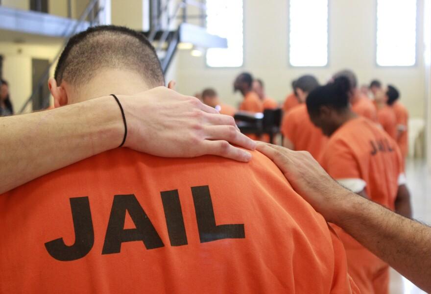 Inmate in orange jumpsuit being embraced