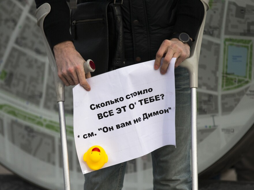 """A man holds a poster saying """"How Much Did it Cost You?"""" with a yellow duck toy in downtown Moscow on Sunday. The protests focused on reports claiming that Prime Minister Dmitry Medvedev has amassed a collection of mansions, yachts and vineyards — and a house for raising ducks."""