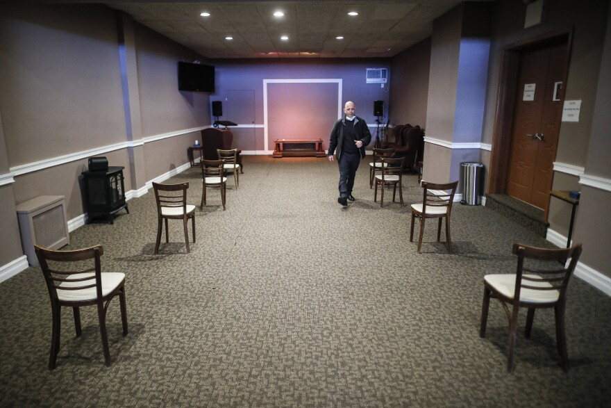 Pat Marmo, owner of Daniel J. Schaefer Funeral Home, walks through a viewing room set up to respect social distancing, Thursday, April 2, 2020, in the Brooklyn borough of New York.