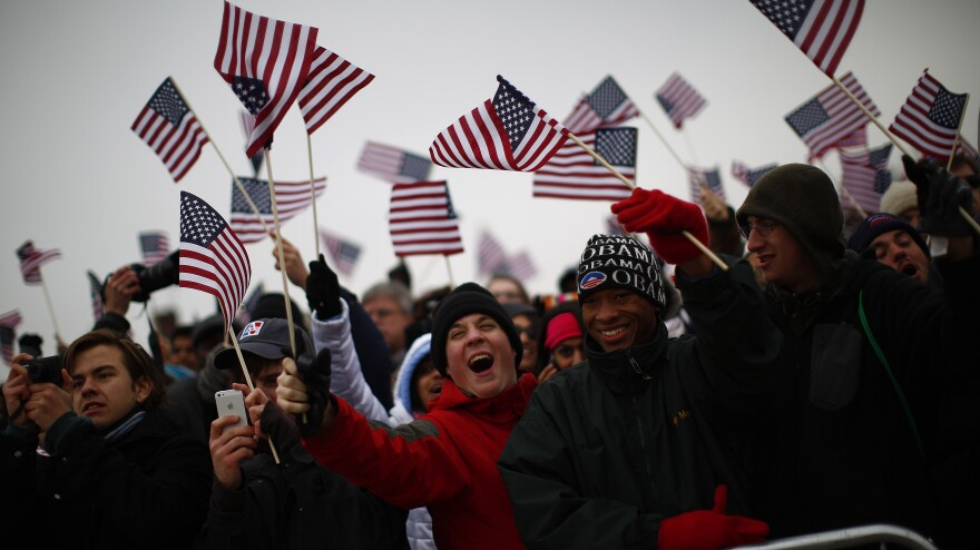 Spectators react on the National Mall during inauguration ceremonies for President Obama.