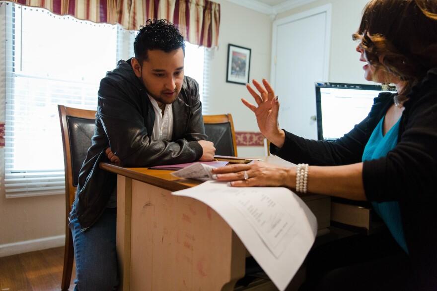 Christian Olvera, a DACA recipient, talks with public notary Enedina Acosta about his taxes.